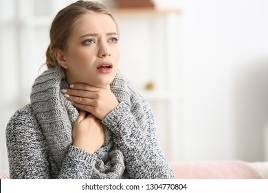 Young woman having asthma attack at home