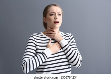 Young woman having asthma attack on grey background