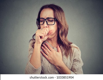 Young woman having asthma problems and coughing badly covering mouth and holding hand on chest.