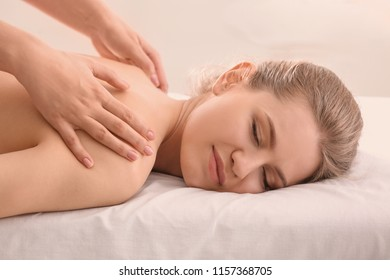 Young woman having back massage in beauty salon