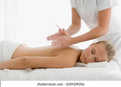 Young woman having back massaged