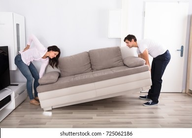 Young Woman Having Backpain While Lifting The Sofa With Her Husband