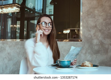 Young woman having a breakfast with coffee and croissant reading newspaper outdoors at the typical french cafe terrace in France