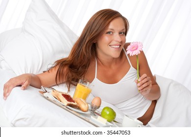 Young woman having breakfast in luxury hotel room