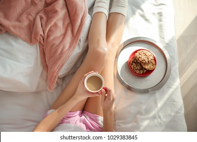 Young woman having breakfast on bed