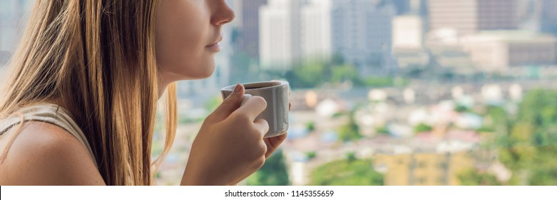 A young woman is having breakfast on the balcony. Breakfast table with coffee fruit and bread croisant on a balcony against the backdrop of the big city BANNER, long format