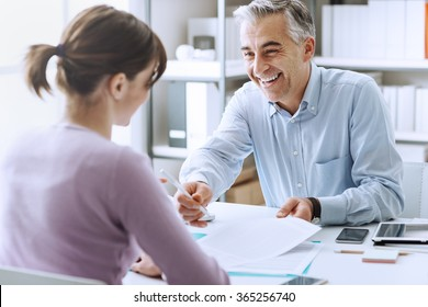 Young woman having a business meeting and signing a contract, recruitment and agreement concept