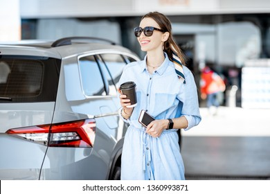 Young woman having a coffee break standing near the car on the gas station