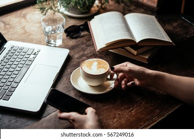 Young woman having a cup of coffee and holding a smart phone  in a cafe