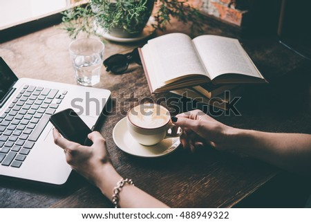 Young woman having a cup of coffee and holding a smart phone  in a cafe. Toned picture