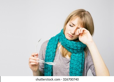 Young woman is having eye ache, she is in depression. She is rubbing her eyes.