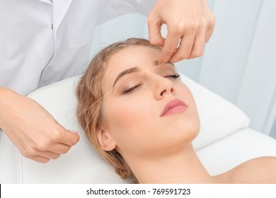 Young woman having eyebrow correction procedure in beauty salon