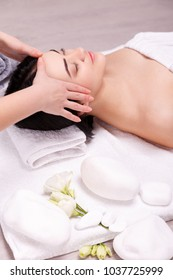 Young woman having face massage in spa