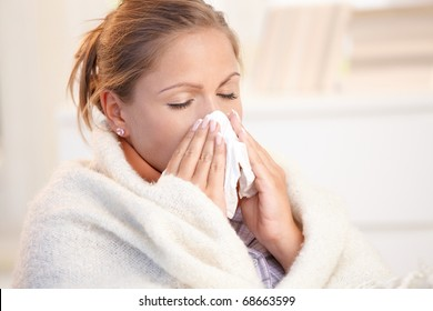 Young woman having flu, feeling bad, blowing her nose, wrapped up in blanket.?