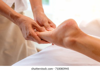 Young woman having foot massage in spa salon, close-up