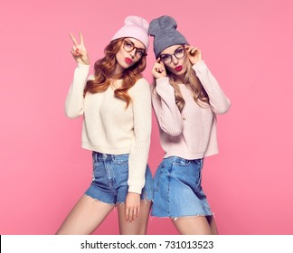 Young Woman Having Fun Crazy Blowing lips make Air Kiss. Fashion. Two Pretty Sisters Best Friends Twins in Stylish Autumn Winter Outfit. Playful Hipster Girls. Cool Model in Cozy Sweater