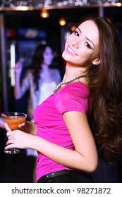 Young woman having fun and dancing at night club disco