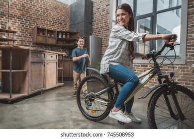 Young woman having fun with her little son and riding bicycle at home