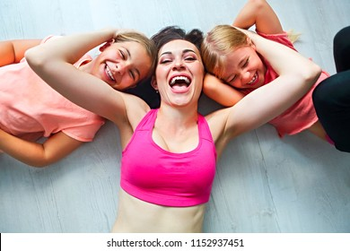 Young woman having fun with kids after yoga. Family sport concept