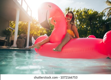 Young woman having fun and laughing on an inflatable flamingo pool float mattress. Attractive woman a summer day in pool.