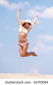 Young woman having fun on a beach. Jumping