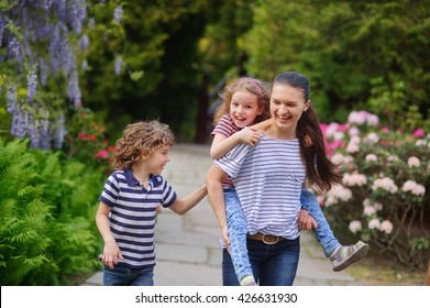 Young woman having fun playing in the park with their children. Boy and girl of primary school age. The family is surrounded by picturesque plants. Games outdoor useful to all.