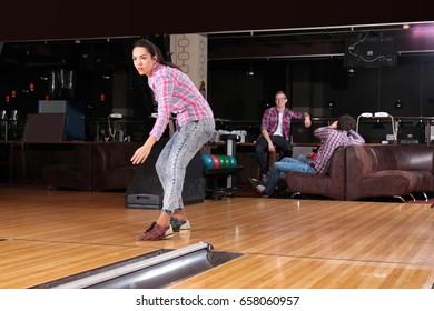Young woman having fun and playing bowling