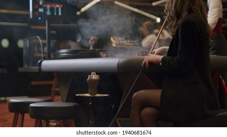 Young woman having fun smoking a hookah, communicating in an oriental restaurant. Lebanon cuisine served in restaurant. Roulette player placing bets at an elite casino. Gambling, nightlife