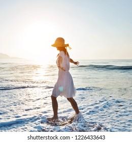 Young woman having fun walking on seaside.