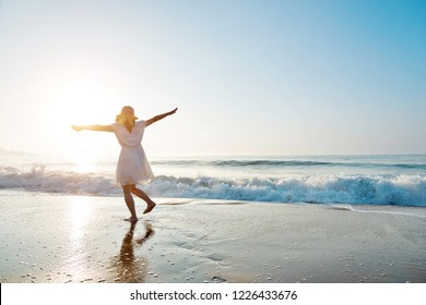 Young woman having fun walking on seaside.