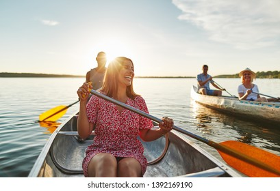 Young woman having fun while canoeing with her boyfriend and friends on a lake on a sunny summer afternoon