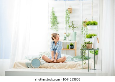 Young woman having a good morning sitting on the bed in the beautiful bright bedroom with green plants and clock