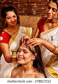 Young woman having head ayurveda spa treatment. Two masseuses.