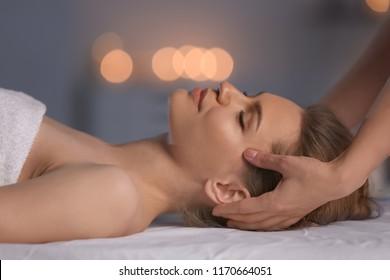 Young woman having head massage in beauty salon