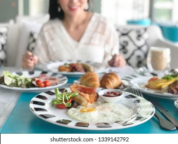 Young woman having healthy breakfast - fried egg, beans, salad, tomatoes, mushrooms, bacon and toast.