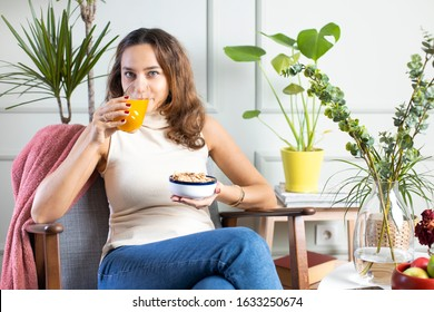 Young woman having healthy breakfast and orange juice in living room. Lifestyle concept.