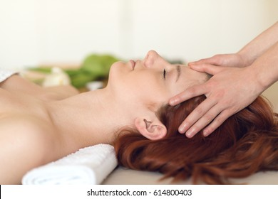 Young woman having her head massaged at a spa center