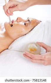 young woman having a honey facial at spa salon