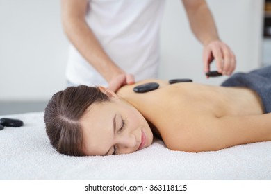 Young woman having a hot stone massage at a spa to de-stress and relax her muscles as hot basalt stones are place along her spine by the therapist