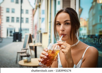 young woman having ice tea in front of a café