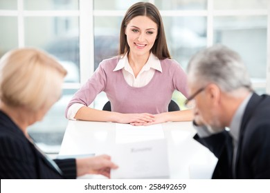 Young woman having an interview or business meeting with employers. Employers examining her CV. Office interior with big window