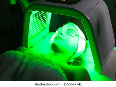 Young woman having LED light facial treatment in beauty salon