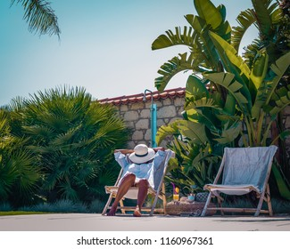 young woman having a nap by the swimming pool sleeping with hat on face, leeping and taking nap concept