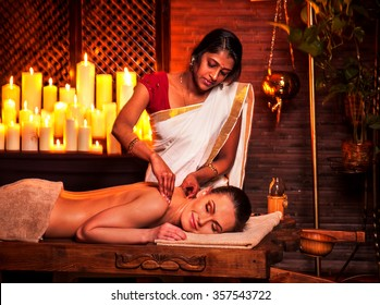 Young woman having oil Ayurveda spa treatment in India salon.