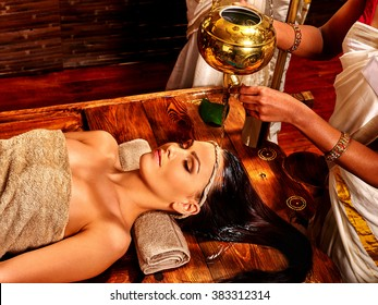 Young woman having oil head Ayurveda spa treatment.