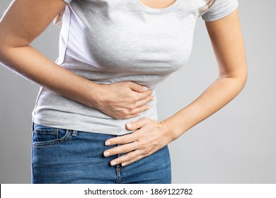 Young woman having painful stomach ache. Chronic gastritis. Stomach or menstrual cramps. Abdomen bloating concept.