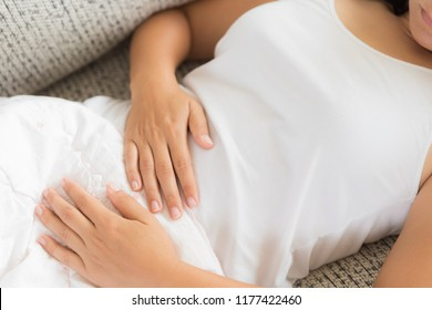 Young woman having painful stomachache lying on sofa at home. Chronic gastritis. Abdomen bloating concept.