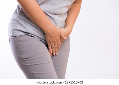Young woman having painful stomachache with hands holding pressing her crotch lower abdomen. Medical or gynecological problems, healthcare concept