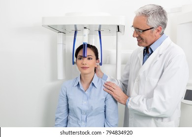 Young woman having panoramic digital x-ray of her teeth with a middle age doctor in the dental office.