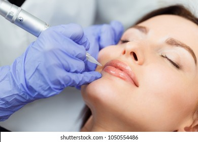 Young woman having permanent makeup on lips in beautician salon. Close up